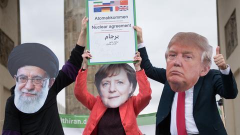 Als Religionsführer Ali Chamenei (l-r), Angela Merkel und Donald Trump verkleidete Schauspieler zeigen im Rahmen einer Anti-Kriegs-Demonstration