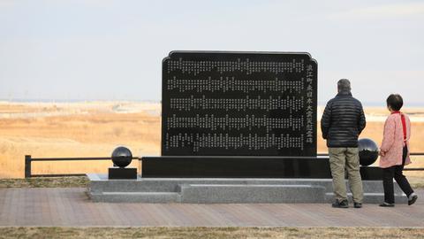 Trauernde an einer Gedenktafel für die Opfer der Ktatstrophe von Fukushima