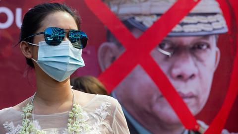 Eine Demonstrantin in Abendkleid steht bei einem Protest gegen den Militärputsch in Myanmar und für die Freilassung der festgesetzten Regierungschefin Aung San Suu Kyi vor einem Plakat mit einem durchkreuzten Porträt des Generals Min Aung Hlaing.