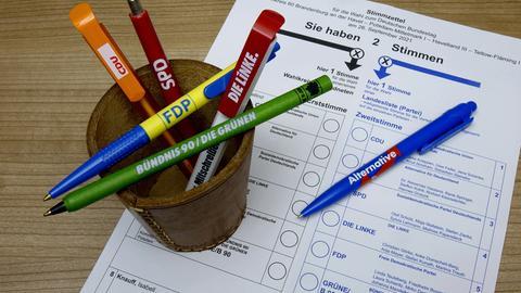 Neben dem Stimmzettel zur Bundestagswahl stehen Becher mit benutzten und unbenutzten Kugelschreibern.
