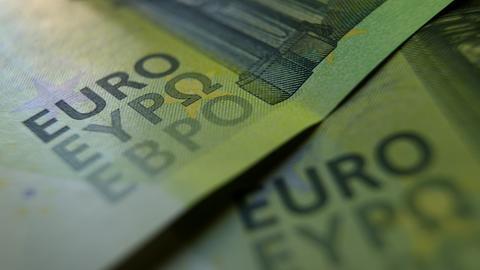 Zwei 100 Euro Banknoten liegen auf einem Tisch.
