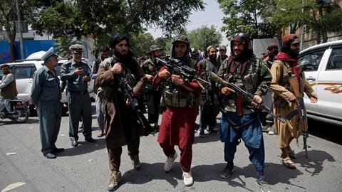Schwer bewaffnete Taliban-Kämpfer patrouillieren vor zwei Verkehrspolizisten (l).