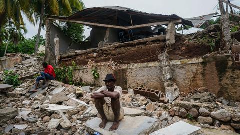 Ein Mann hockt auf den Trümmern des durch das Erdbeben zerstörten Krankenhauses in Fleurant.