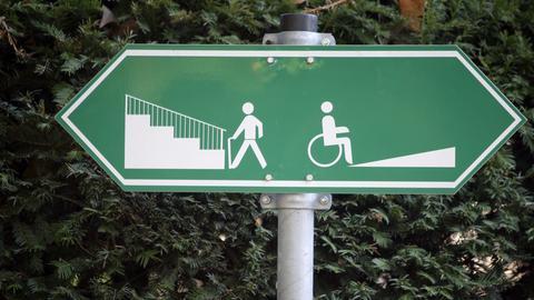 Ein Schild weist am 20.10.2008 in Frankfurt (Hessen) darauf hin, dass Fußgänger links eine Treppe und Rollstuhlfahrer rechts eine Auffahrt benutzen können.