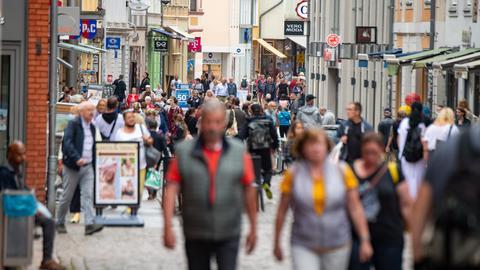 Eine große Menschenmenge geht durch die Einkaufstraße im Zentrum.