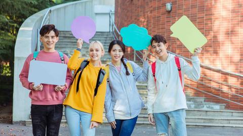 Vier junge Leute halten Sprechblasen-Symbole hoch