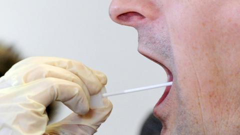 Eine Polizistin entnimmt bei einem Mann mit einem Wattestäbchen eine DNA-Probe.