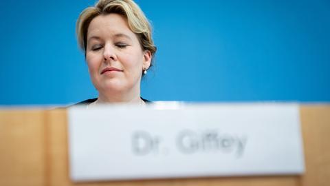 """Franziska Giffey (SPD), Bundesministerin für Familie, Senioren, Frauen und Jugend, sitzt bei der Vorstellung des Zwischenberichts zur Konzertierten Aktion Pflege in der Bundespressekonferenz hinter ihrem Namensschild mit der Aufschrift """"Dr. Giffey""""."""