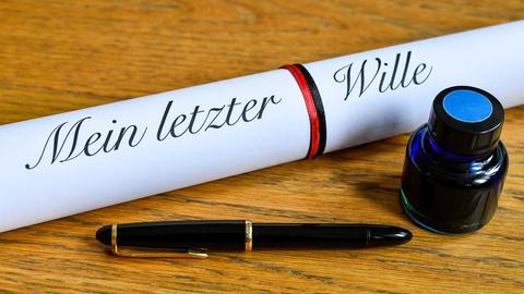 """Die Wörter """"Mein letzter Wille"""" sind neben einem Fueller und einem Tintenfass auf einem weissen Blatt Papier zu lesen (gestellte Szene)."""