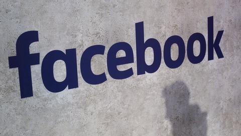 Der schatten eines vorbeigehenden Mannes zeichnet sich vor einem Logo von Facebook ab.