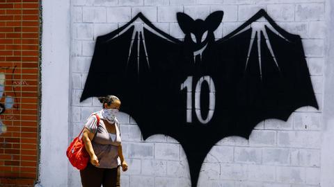 Eine Frau läuft vor einer Wand mit Fledermaus-Graffiti vorbei.