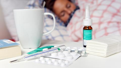 Medikamente und ein Fiberthermometer liegen im Vordergrund während man im Hintergrund einen an Grippe erkrankten Patienten im Bett liegen sieht.