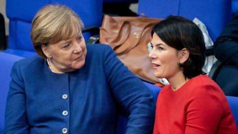 Bundeskanzlerin Angela Merkel (CDU) und Annalena Baerbock (r), Bundesvorsitzende von Bündnis 90/Die Grünen, nehmen an der Sitzung des Bundestages teil.