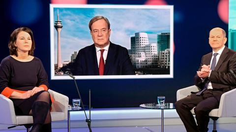 Unions-Kanzlerkandidat Armin Laschet wird auf einem Fernsehschirm gezeigt, während die Mitbewerbern von Grünen und SPD, Annalena Baerbock und Olaf Scholz im Fernsehstudio bei einer Diskussionsrunde des WDR-Europaforums in Berlin sitzen. Es war das erste Aufeinandertreffen der drei Kanzlerkandidaten