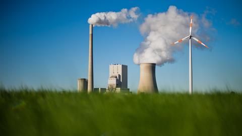 Ein Windrad steht auf einem Feld vor einem Kohlekraftwerk