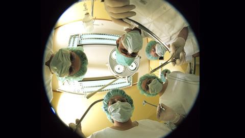 Ärzte beugen sich während einer Operation über den Patienten