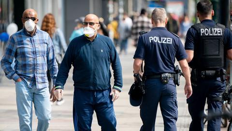 Passanten mit Mund-Nasen-Schutz geht auf dem Kudamm an Polizeibeamten vorbei. Als letztes Bundesland führt Berlin auch eine Maskenpflicht in Geschäften ein.