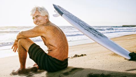 Ein Älterer Mann sitzt mit einem Surfbrett am Strand