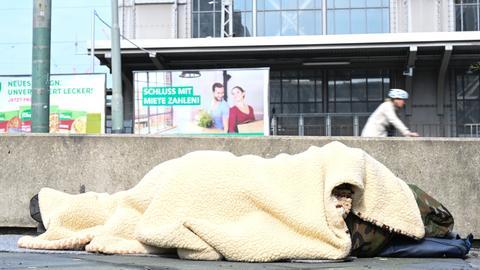 Ein Obdachloser schläft nahe des Frankfurter Hauptbahnhofs hinter einer Betonmauer.