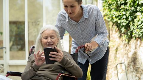 Seniorin zeigt Ihrer Pflegekrin etas auf dem Handy