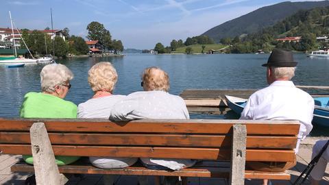 Rentner sitzen an einem sonnigen Tag auf einer Bank und geniessen den Blick auf den Tegernsee in Rottach Egern.