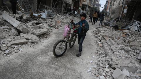 Syrien, Ghuta: Ein Kind schiebt sein Fahrrad an Gebäuden vorbei, die durch Angriffe der syrischen Luftwaffe zerstört wurden.