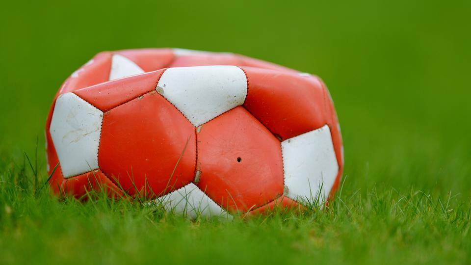 Die Luft ist raus - Platter Fußball liegt auf dem Fußballplatz.