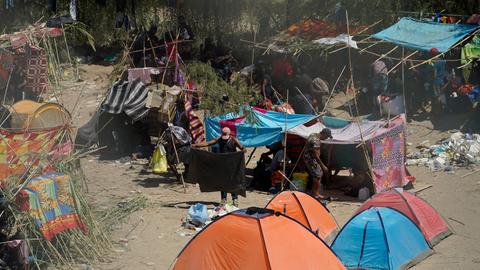 Zelte und improvisierte Hütten stehen in einer steppenartigen Landschaft