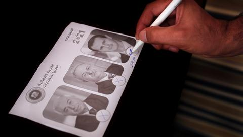 Ein syrischer Mann, der im Libanon lebt, steht in einer Wahlkabine und kreuzt ein Kästchen unter einem Porträt des syrischen Präsidenten Assad auf seinem Stimmzettel an. Die arabische Aufschrift: «Wir opfern für dich» steht über den abbildeten Porträts der Kandidaten. Vor der syrischen Präsidentschaftswahl am 26. Mai hat in den Botschaften im Ausland die Stimmabgabe begonnen.
