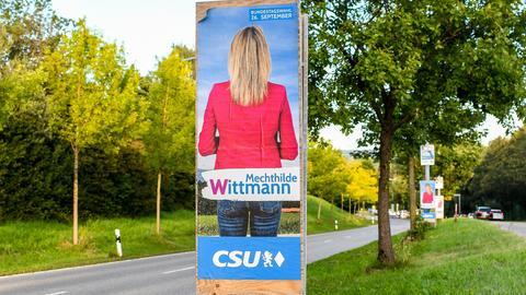 Wahlplakat einer CSU-Kandidatin: Frau in rosa Jacke von hinten