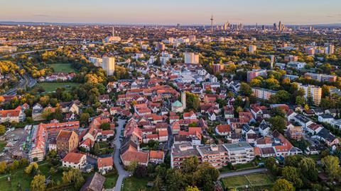 Der Stadtteil Niederursel im Nordwesten Frankfurts bei Sonnenuntergang, mit Skyline im Hintergrund