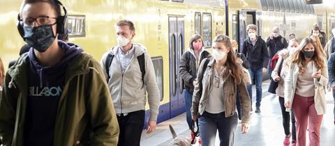 Pendler kommen am Morgen mit verschiedenen Gesichtsbedeckungen am Hauptbahnhof an. In Bussen und Bahnen sowie beim Einkaufen gilt in Hamburg von diesem Montag an eine Maskenpflicht.