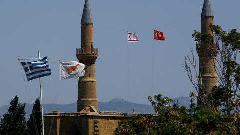 Griechische und zypriotische Flaggen flattern im Wind im südlichen Teil. Währenddessen im Norden, im türkisch besetzten Gebiet, eine türkische und eine türkisch-zypriotische Flagge wehen.