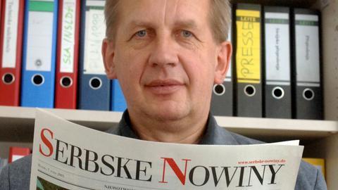 """Der Chefredakteur der sorbischen Abendzeitung """"Serbske Nowiny"""", Benedikt Dyrlich, blickt über sein Blatt zum Fotografen."""