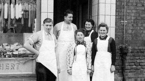 Der stolze Firmengründer Hans Reichert mit Mitarbeitern vor seinem ersten Laden in Frankfurt Höchst