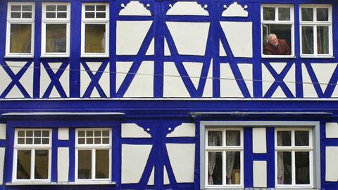 """Ein Mann schaut in Wertheim aus dem Fenster eines Hauses mit blau eingefärbten Fachwerk. Die Holzbalken sind mit """"Smalte"""" gefärbt, einem kobalthaltigem Glas, das fein gerieben als Farbpigment benutzt wurde. Bisher sind lediglich in der Schweiz vier Gebäude mit dieser """"Smalte""""-Färbung bekannt."""