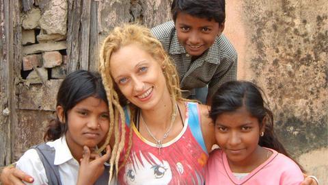 Stella Deetjen sitzt mit Waisenkindern vor einem Heim in der indischen Stadt Benares.