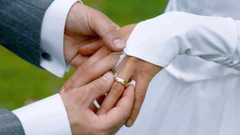 Ein Bräutigam streift bei der Trauung seiner Braut den Ehering über den Finger.