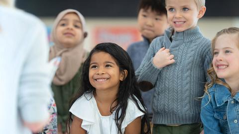 Mehrere Kinder schauen gebannt auf eine Vorleserin