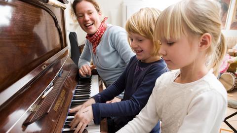 Mutter mit Kindern am Klavier