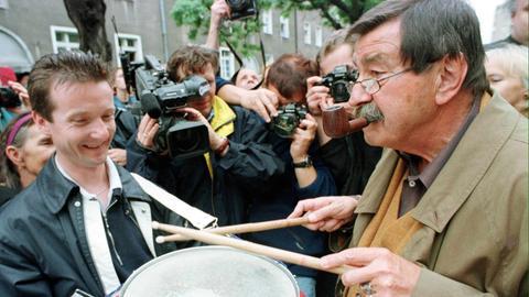 Günter Grass spielt vor seinem Elternhaus in Danzig eine Blechtrommel.