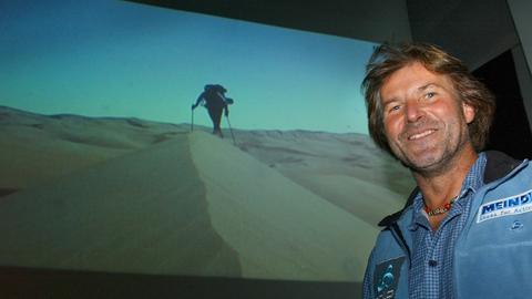 Bruno Baumann vor einer Dia-Leinwand mit einer Wüstenaufnahme