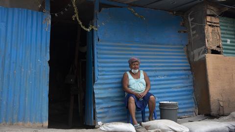 eine grauhaarige Frau sitzt mit Mund-Nasen-Schutz vor ihrem Wellblechhaus