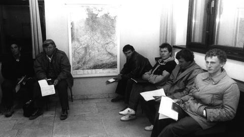 Schwarz-weiß-Aufnahme von sechs Männern, die vor einer Deutschlandkarte im Deutschen Konsulat in Moskau sitzen.