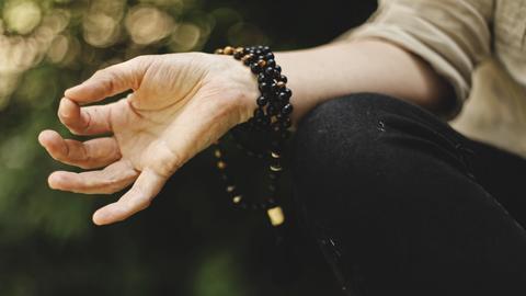 hand mit Armband beim Meditieren