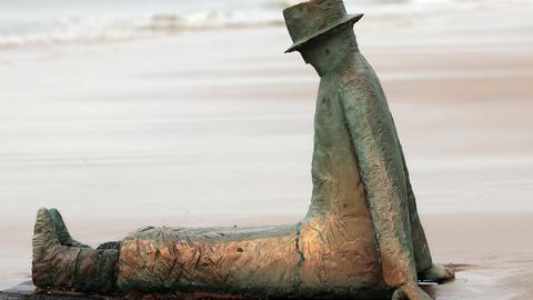 Die Plastik eines sitzenden Mannes am Strand
