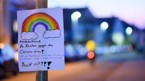 Schild mit handgemaltem Regenbogen auf einer Straße