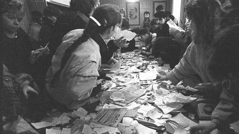 Menschen stehen um einen Tisch herum, auf dem Stasi-Unterlagen liegen