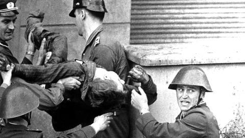 DDR-Grenzposten tragen den leblosen Körper von Peter Fechter weg, nachdem er zuvor bei einem Fluchtversuch an der Mauer von DDR-Volkspolizisten niedergeschossen worden war.
