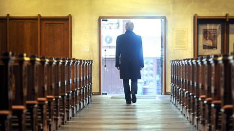 ein Mann verlässt eine leere Kirche